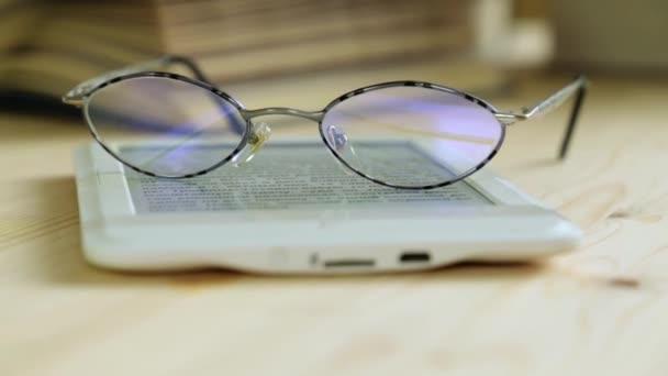 E-knihu, brýle a papírové knihy, detail