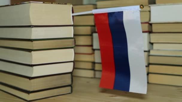 Russische Flagge auf dem Hintergrund von Büchern. Flagge Russlands und Papierbücher.