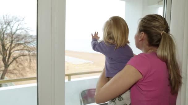 Šťastná žena a dítě se dívá z okna.