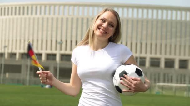 Fotbalový fanoušek s německou vlajkou. Žena s míčem a vlajka Německa.
