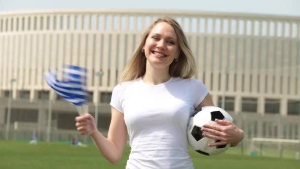 Football fan with the flag of Greece. Woman with a Greek flag and a soccer ball.