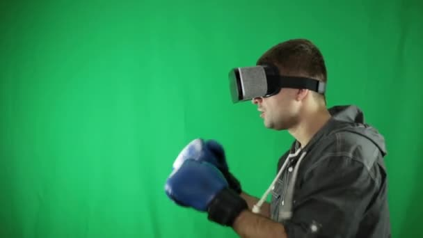 744670b555f2 A man in virtual reality glasses and boxing gloves on a green background.–  stock footage
