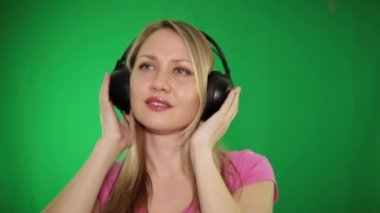 Woman listening to music on headphones on a green background.