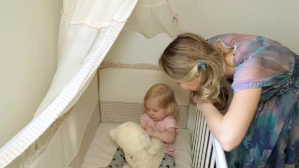 Žena a dítě na lůžku. Maminka s dítětem v ložnici