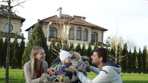 Šťastná mladá rodina s dítětem na pozadí krásný domov.
