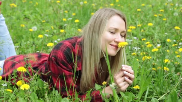 Young woman smelling a flower lying on a green grass.