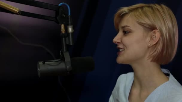 Photo Young woman DJ talking in microphone in studio on radio station