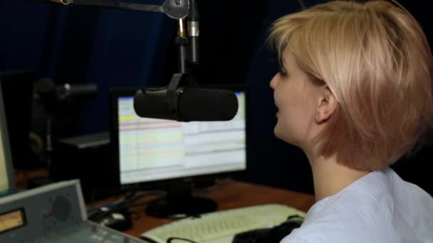 Photo A female DJ speaks into a microphone in a studio on a radio station