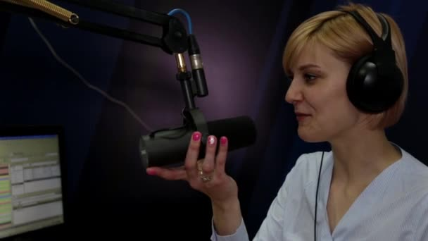 Photo A female DJ speaking into a microphone on the air of a radio station