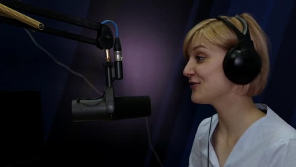 Photo A young woman with a DJ, a speaker speaks into a microphone on the air of a radio station