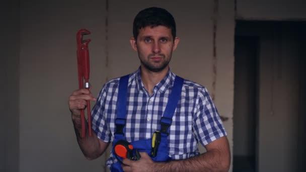 Samec instalatéra s velkým instalatérským nářadím. Portrét instalatéra.