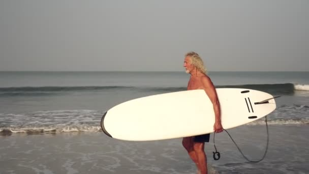 Active sports pensioner. Mature gray-haired man is surfing. Old man with a surfboard