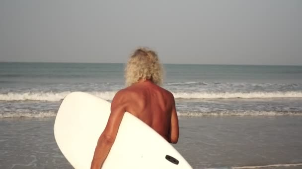 Portrait of a mature man with a surf. Grandfather on the beach with a surfboard