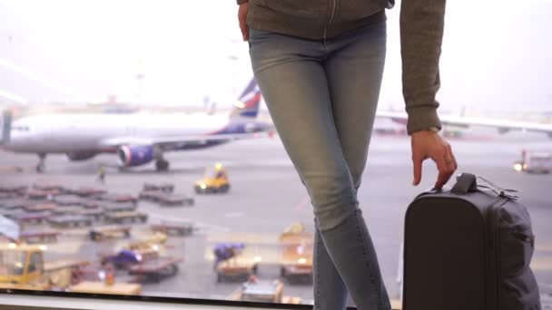 Woman tourist with a small suitcase in an airport terminal in front of airplanes