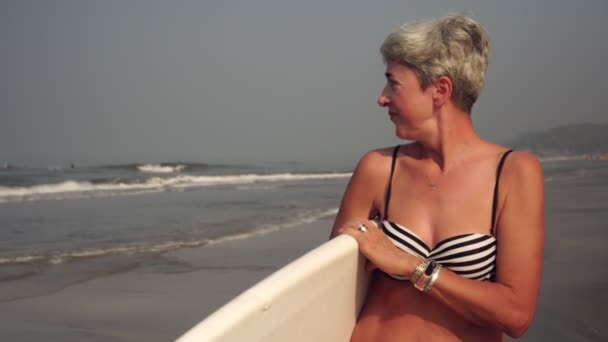 Attraktive ältere Frau Großmutter ist zu Fuß mit Brandung am Strand