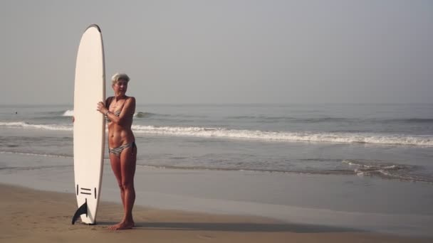 Slender attractive mature woman with surfboard on the beach