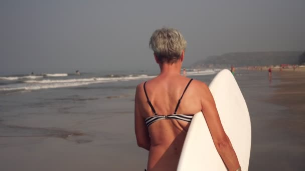 Attractive mature woman grandmother in a swimsuit is surfing along the beach