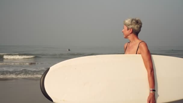 Grandmother, mature woman on the beach with a surfboard
