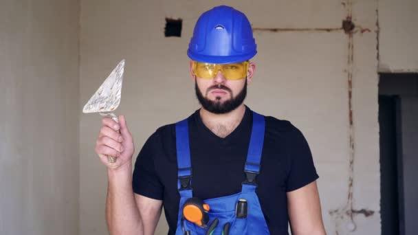 Portrét seriózního mužského stavitele sádry s plnovousem na staveništi