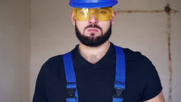 Portrét seriózního instalatéra. Stavební dělník s klešťovým klíčem