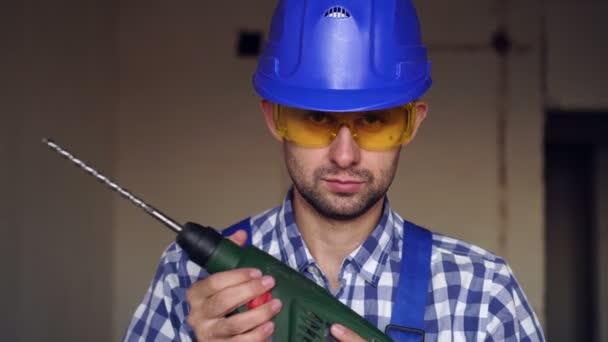 Vážný muž stavitel s elektrickým kladivem vrták. Portrét stavitele na staveništi