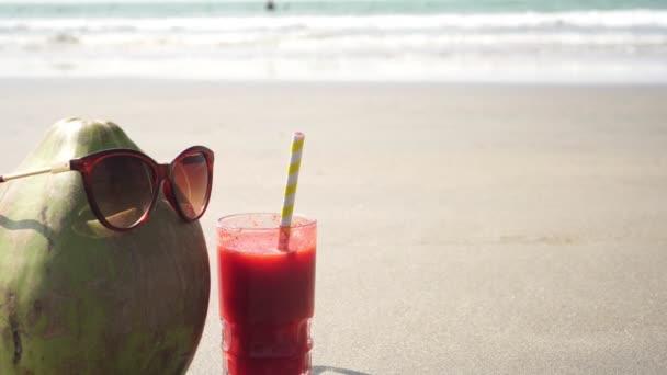 Kókusz napszemüvegben a tengernél egy pohár gyümölcslével. Trópusi strand