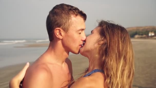 Young couple in love kisses on the beach. Newlyweds, honeymoon at sea