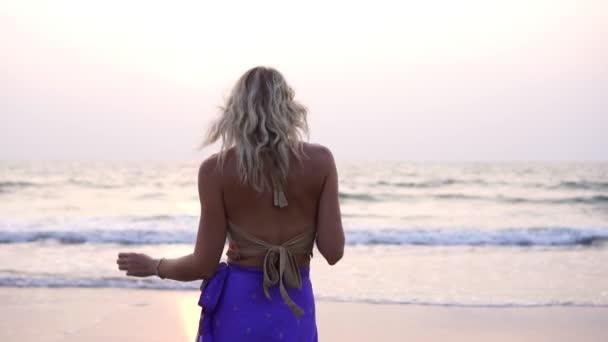 Schöne junge Frau tanzt am Strand. Eine Frau tanzt einen orientalischen Tanz.