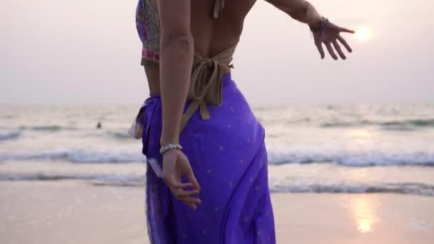 Eine Frau tanzt am Strand bei Sonnenuntergang einen orientalischen Tanz