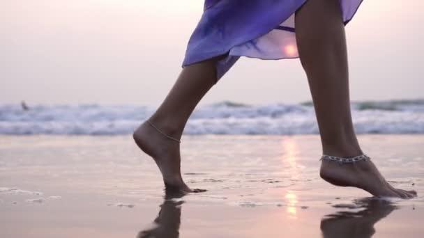 Eine junge Frau tanzt am Abend auf dem Meer bei Sonnenuntergang