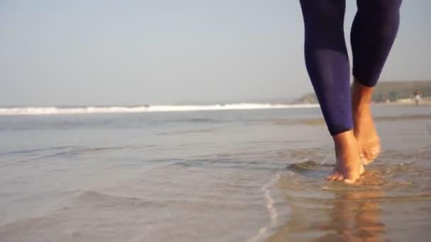 Ženské nohy jdou podél pobřeží. Žena kráčí podél moře na písečné pláži