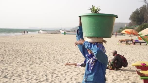 Arambol, India - February 2020. A woman seller carries a basket with fruit on her head