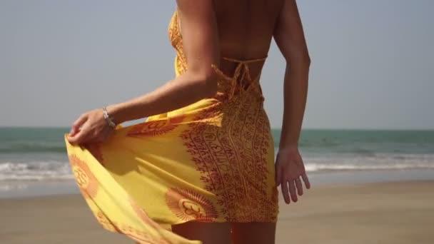 Junge sexy Frau tanzt in einem Kleid am Strand. Mädchen tanzen am Strand