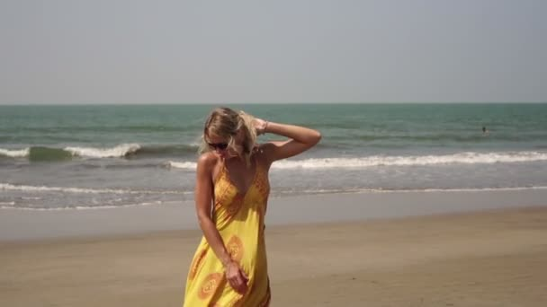 Schöne junge Frau tanzt am Strand. Mädchen tanzen am Strand