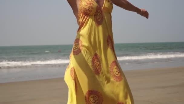 Schöne sexy Frau tanzt in einem Kleid an einem tropischen Strand. Tanz des Mädchens am Meer