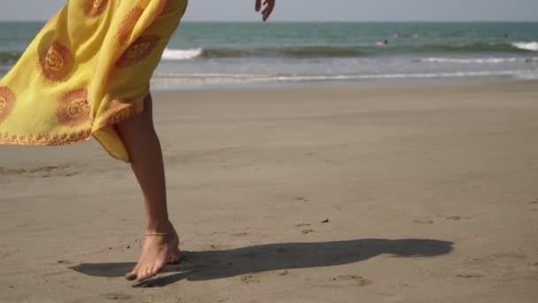 Junge schöne Frau tanzt im hellen Kleid am Sandstrand