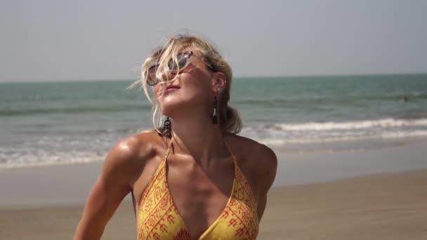 Schöne sexy blonde Frau tanzt in einem Kleid an einem tropischen Strand