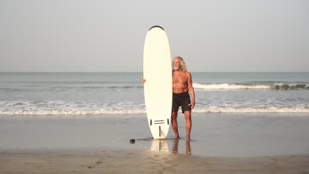 Grandfather, adult man, old man with a surfboard on the beach. Senior citizen surfer.