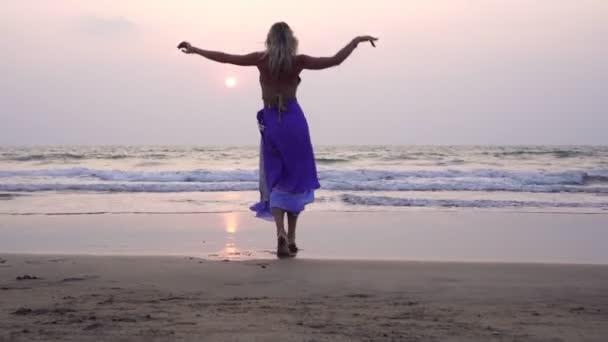 Junge schöne Frau in ethnischer orientalischer Kleidung tanzt am Meeresstrand