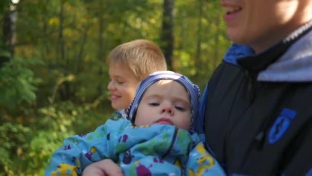 Mladá rodina, procházky v parku, otče účetní syna v náručí