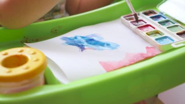 kis gyerek ilyenkor lerajzol festékek egy papírlapra