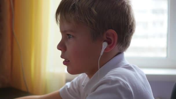 dítě poslouchá hudbu na smartphone ve sluchátkách a chmel hlavu v domácnosti
