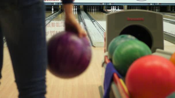 Dívka hází míč v bowlingu. 4k