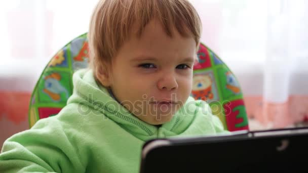 happy child watching cartoons on the tablet and smiling