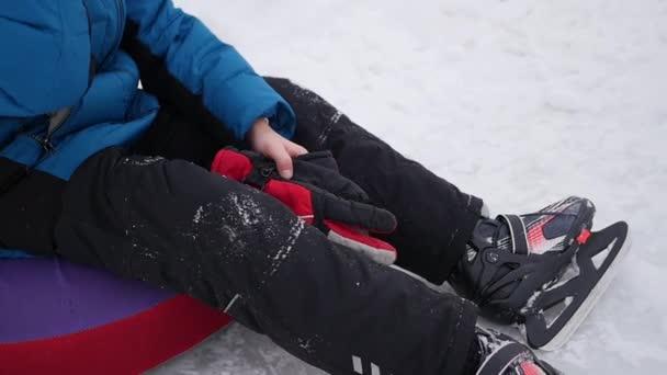a boldog gyermek ül, pihenő- és mosolyog a jégpálya a korcsolyát