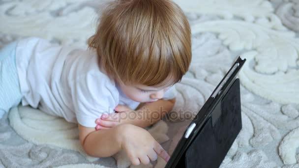 child looks cartoons on tablet pc on floor