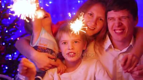 Famiglia felice illuminato stelle filanti alla festa. In sottofondo, luci del bokeh e ghirlande di abete di Natale