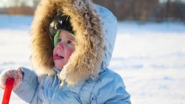 šťastné dítě s fun smát v zimě parku za slunečného dne. Snow zimní krajina. venku