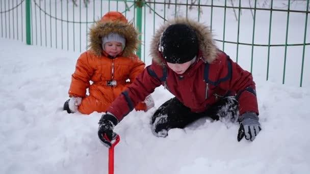 šťastné děti hrají v parku na slunný zimní den. Zasněžená zimní krajina. venku