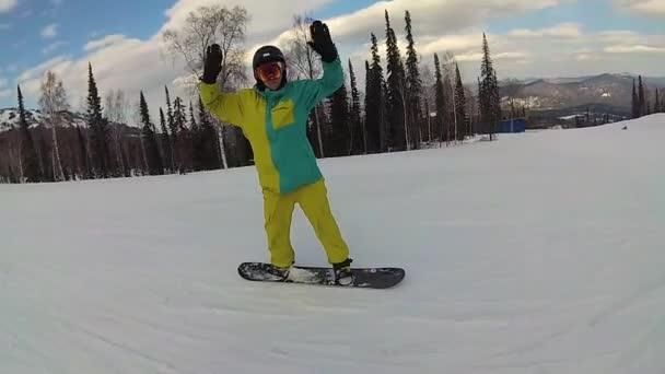 Glücklicher Mann auf einem Snowboard, der bei sonnigem Wetter den Hang hinunterrutscht